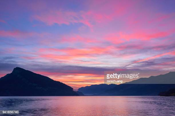 lake geneva in dramatic sky at sunset - purple stock pictures, royalty-free photos & images