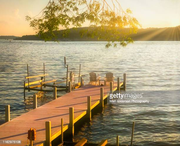 lake geneva pier with chairs at sunset - wisconsin stock pictures, royalty-free photos & images