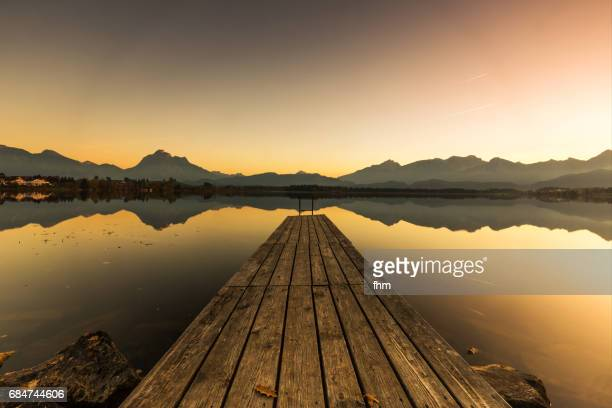 Lake Hopfen with a jetty and Alps mountains with idyllic sunset (Allgäu/ Bavaria/ Germany)