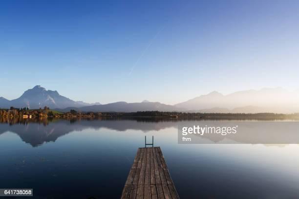 lake hopfen with a jetty and the alps in the background (allgäu/ bavaria/ germany) - bootssteg stock-fotos und bilder