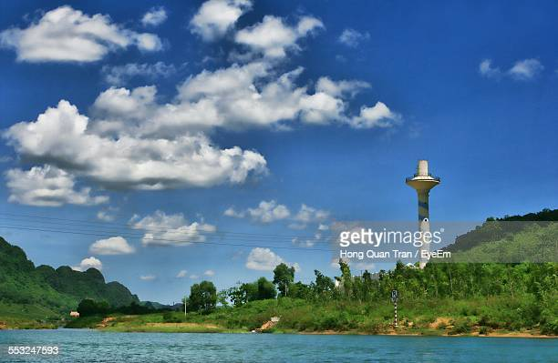 lake in front of lighthouse on field against cloudy blue sky - hong quan stock pictures, royalty-free photos & images