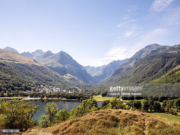 Lake in the Pyrenees surrounded by mountains and forest with a town on the shore, Fracia