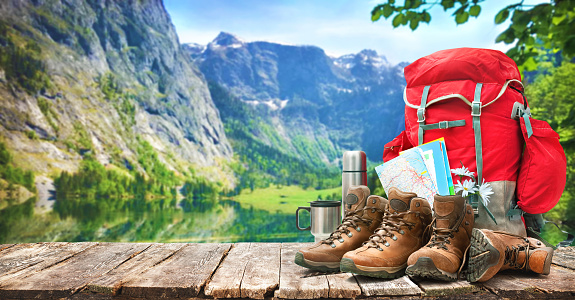 lake landscape with big backpack and trekking boots 966378690