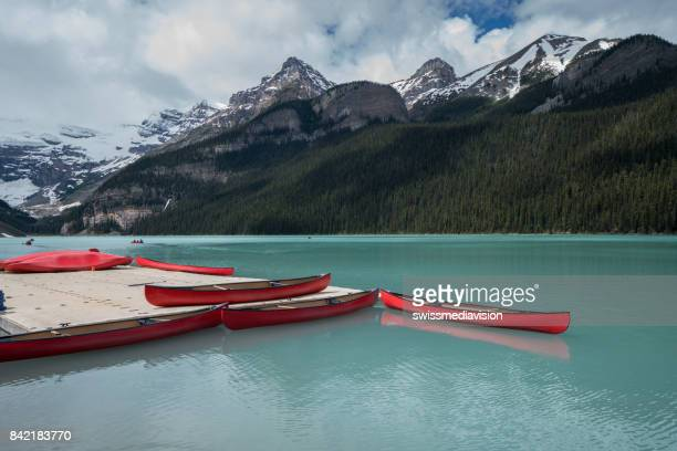 lake louise and red canoe at banff national park, canada - lake louise lake stock photos and pictures