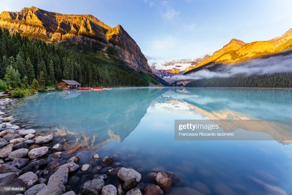 Lake Louise at sunrise, calm water and light on the mountain tops. Banff, Alberta, Canada. : Stock-Foto