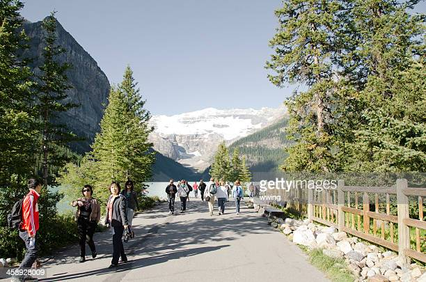 lake louise tourists on walkway - chateau lake louise stock photos and pictures
