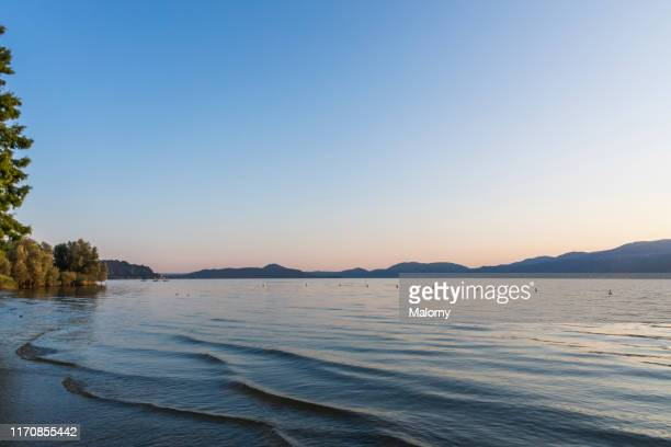 lake maggiore at sunset, mountain range in the background. - lakeshore stock pictures, royalty-free photos & images