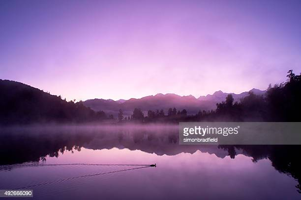 lake matheson and the southern alps at dawn - purple stock pictures, royalty-free photos & images