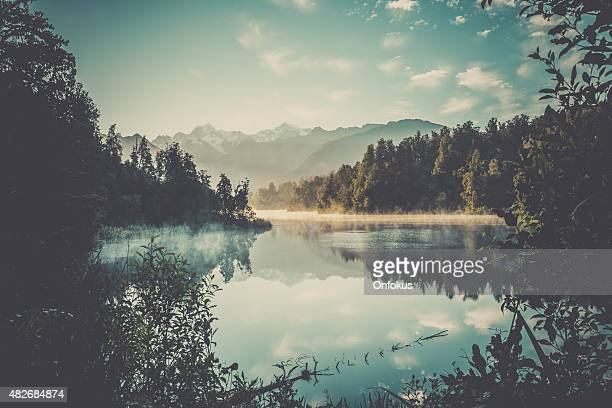 lake matheson nature panorama at sunrise, new zealand - landscape scenery stock photos and pictures