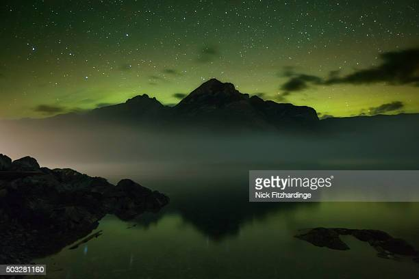 Lake Minnewanka at night with a faint aurora borealis in the sky, Banff National Park, Alberta, Canada