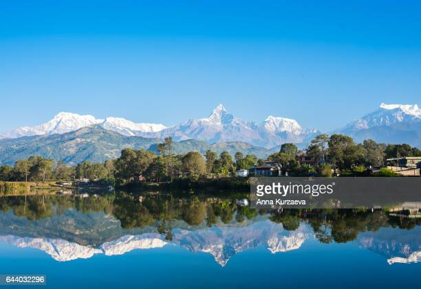 lake phewa in pokhara, nepal, with the himalayan mountains in the background, including machhapuchhre and annapurna - pokhara stock pictures, royalty-free photos & images