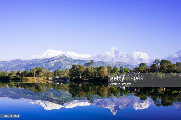 lake phewa in pokhara, nepal, with the himalayan mountains in the background, including machhapuchare and annapurna - machapuchare stock photos and pictures