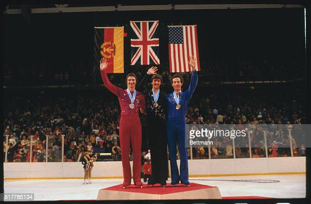 Great Britain's Robin Cousins is flanked by East Germany's Jan Hoffman and the USA's Charlie Tickner at medal presentation ceremonies 2/21 Cousins...