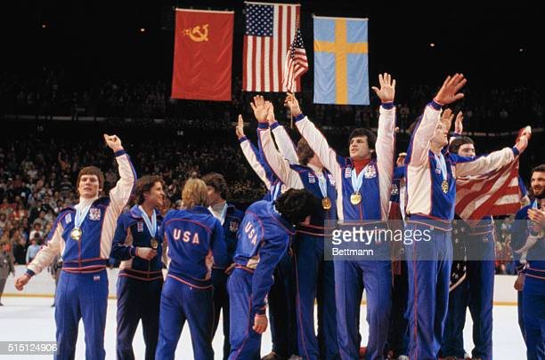 The American Olympic Hockey Team crowds onto the center podium with fingers pointed skyward designating their Number One status at Olympic awards...