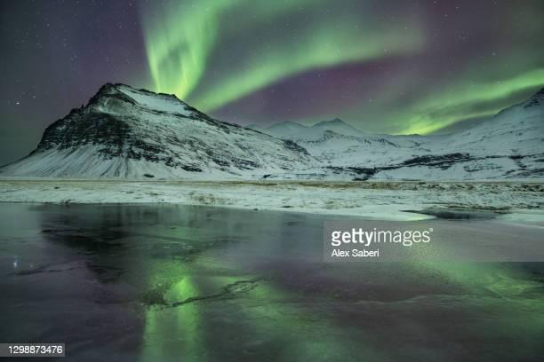 a lake reflects the aurora borealis. - alex saberi foto e immagini stock