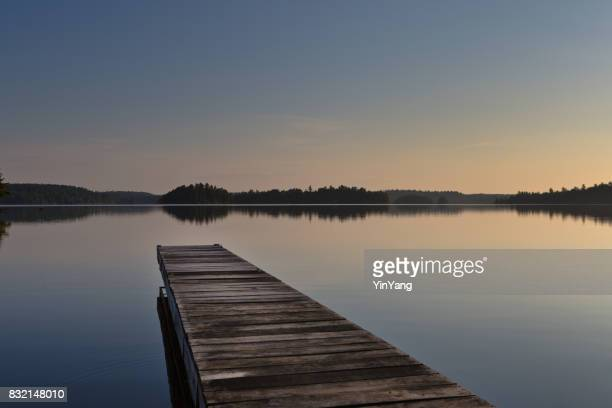 lake scene  and boat dock at ely, boundary water canoe area, minnesota, usa at sunrise - boundary waters canoe area stock pictures, royalty-free photos & images