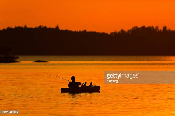 lake scene fisherman fishing at ely, boundary water canoe area, minnesota, usa at sunset - boundary waters canoe area stock pictures, royalty-free photos & images