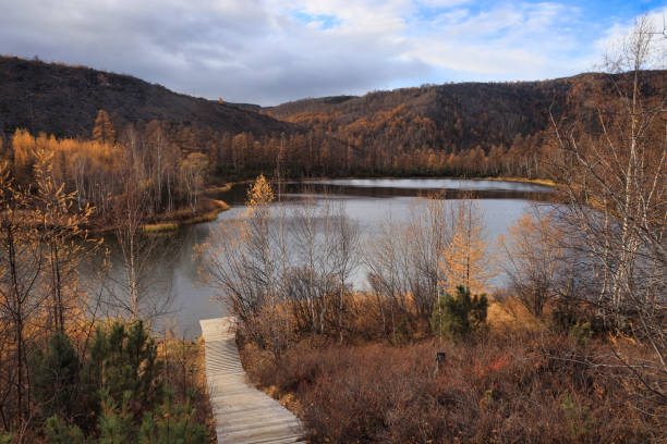 Lake surrounded by forested mountains in autumn, Esso, Kamchatka Krai, Russia