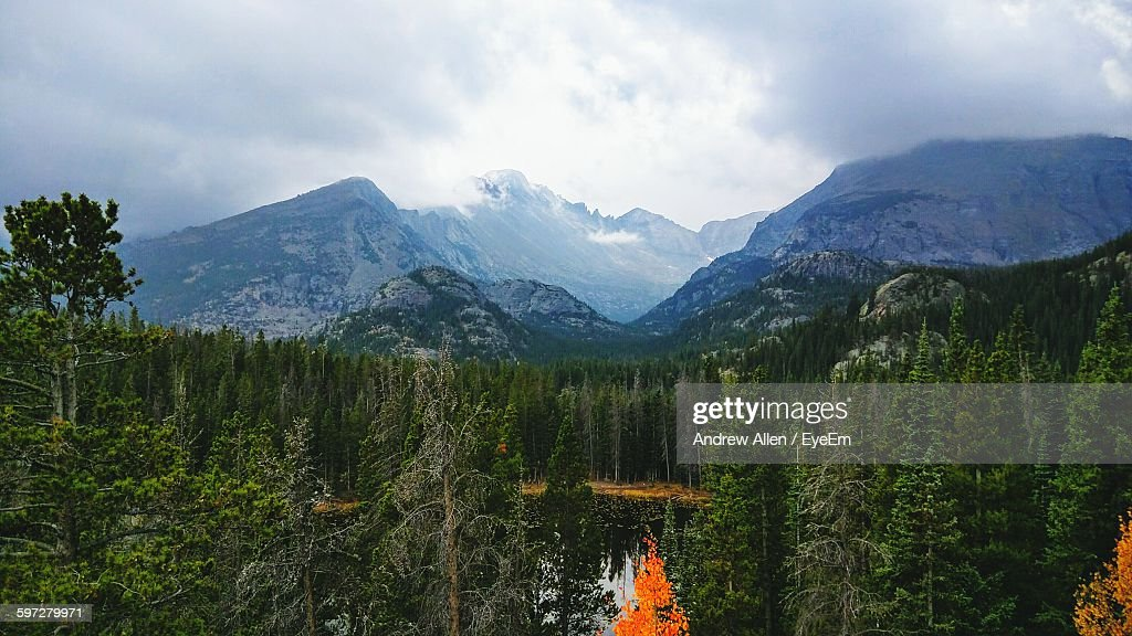 Lake Surrounded By Trees Against Mountains Against Cloudy Sky : Stock Photo