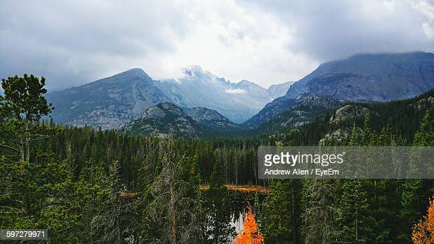 Lake Surrounded By Trees Against Mountains Against Cloudy Sky
