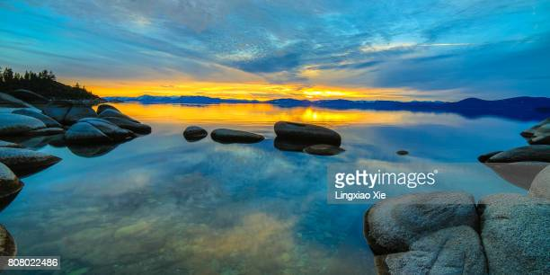 lake tahoe reflection at dusk with rocks, nevada - lake tahoe stock photos and pictures
