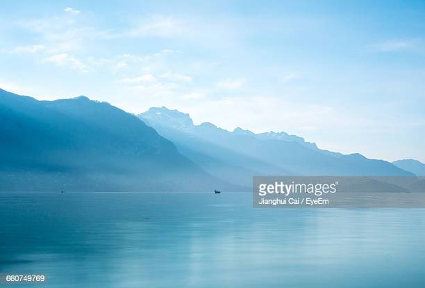 Lake With Mountain Range In Background Against Cloudy Sky