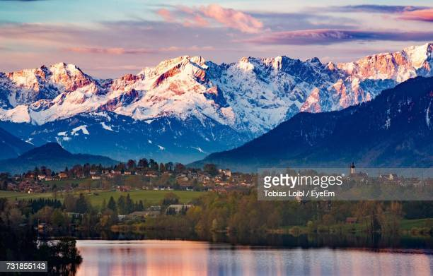 lake with trees and houses against snowcapped mountains - loibl stock-fotos und bilder