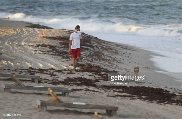 Lake Worth lifeguard wearing a protective mask walks along a deserted beach as Palm Beach County officials announced that all county beaches are...