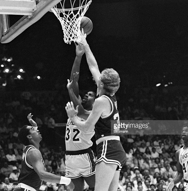 Laker guard Magic Johnson puts up a shot over Celtic forward Larry Bird for 2 points in first quarter action