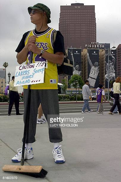 Lakers fan Eugen Carino stands with a broom outside the Staples Center in Los Angeles CA 27 May 2001 before the start of game four of the NBA Western...