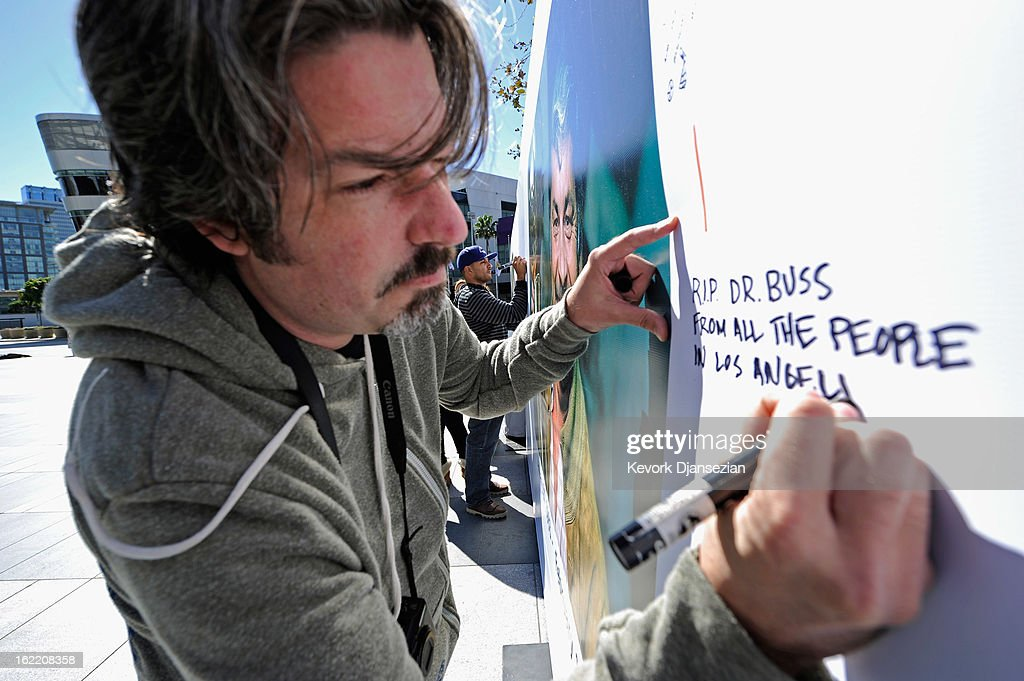 Lakers fan Mike Delahaut writes a personal message on the Dr. Buss Memorial Banners in the Nokia Plaza at L.A. Live, directly across the street from Staples Center on February 20, 2013 in Los Angeles, California. The Lakers will hold a memorial service to celebrate the life of longtime owner Jerry Buss at the Nokia Theater on Thursday, for invited guests only. Dr. Buss died at the age of 80 on Monday following an 18-month battle with cancer.