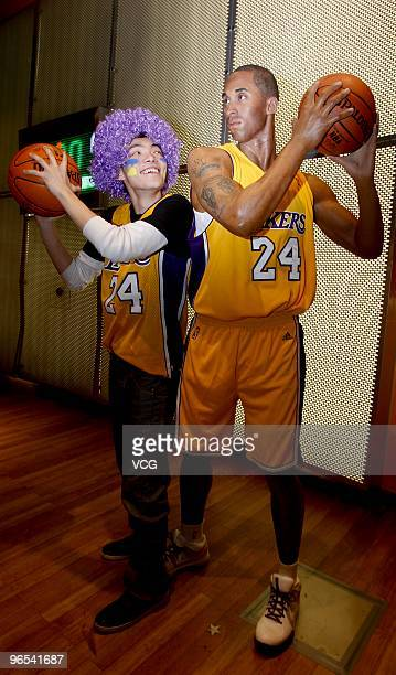 Lakers fan poses for photos with the waxwork of American shooting guard Kobe Bryant at Madame Tussauds on February 9, 2010 in Shanghai of China.