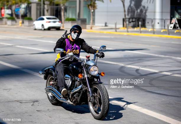 Lakers fan sports his Lakers jersey while riding his motorcycle by fellow fans outside the Staples Center after their championship win the night...