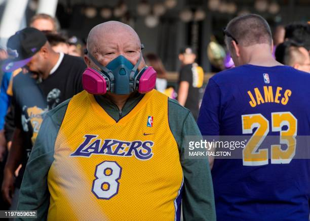 A Lakers fan wears a mask to protect against the Coronavirus as he pays his respects at a Staples Center memorial wall to NBA legend Kobe Bryant who...