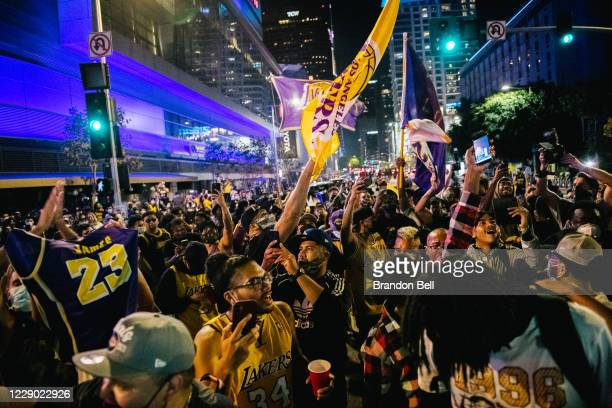Lakers fans celebrate in front of the Staples Center on October 11, 2020 in Los Angeles, California. People gathered to celebrate after the Los...