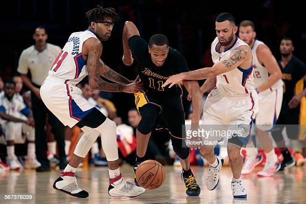 LOS ANGELES CA FRIDAY OCTOBER 31 2014 Lakers forward Wesley Johnson dribbles through Clippers defenders Chris DouglasRoberts left and Jordan Farmar...