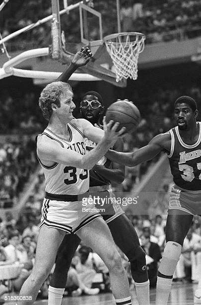 Lakers' James Worthy and Earvin 'Magic' Johnson move in attempting to block Larry Bird of the Celtics in 1st quarter of their game at the Boston...