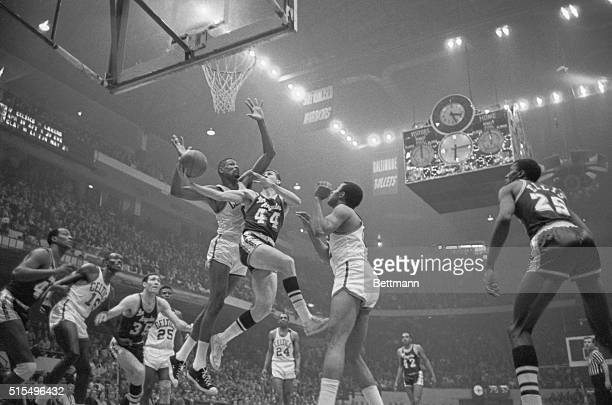 Lakers' Jerry West is guarded closely by Celtics' Bill Russell as he goes in for a layup 3rd period 1st game of championship playoffs of the NBA...