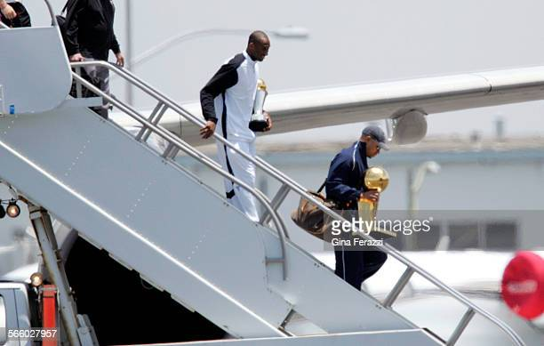 Lakers Kobe Bryant carries his MVP trophy as teammate Derek Fisher carries the championship trophy upon arriving at LAX the morning after beating...