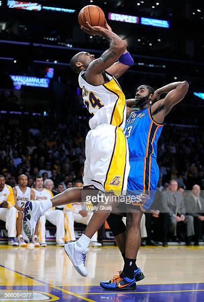 Lakers Kobe Bryant makes a behind the basket shot in front of Thunder's James Harden in the 2nd quarter at the Staples Center Sunday