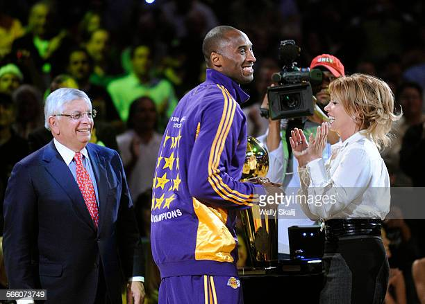 Lakers Kobe Bryant smiles after receiving his championship ring from NBA commisioner David Stern left and Jeanie Buss at the Staples Center Tuesday