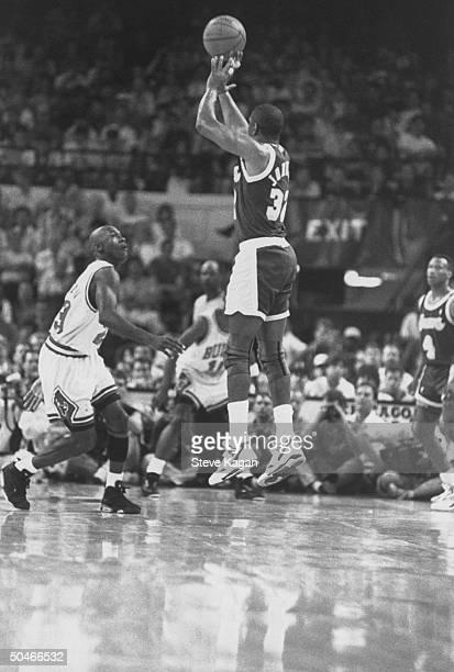 LA Lakers' star Magic Johnson making a jump shot as Chicago Bulls' star Michael Jordan rushes in to block it during NBA championship game at Chicago...
