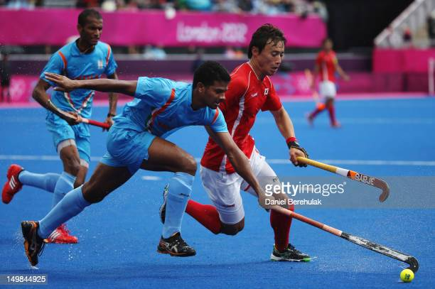 Lakra Birendra of India and Hong Eun Seong of South Korea fight for the ball during the Men's Hockey match between India and South Korea on Day 9 of...