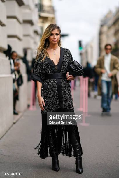 Lala Rudge wears a black kimono dress with shiny embroidery, fringes and lace, high leather boots, earrings, a necklace , outside Ralph & Russo,...