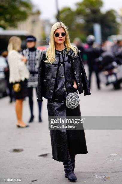 Lala Rudge wears a black leather jacket, a flower shaped bag, a black dress, outside Chanel, during Paris Fashion Week Womenswear Spring/Summer 2019...