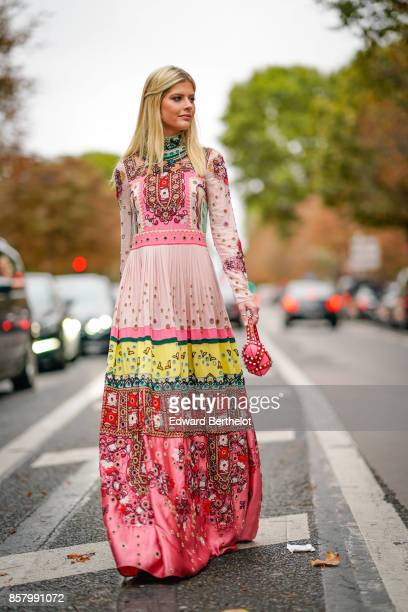 Lala Rudge wears a pink dress with colored prints outside Valentino during Paris Fashion Week Womenswear Spring/Summer 2018 on October 1 2017 in...