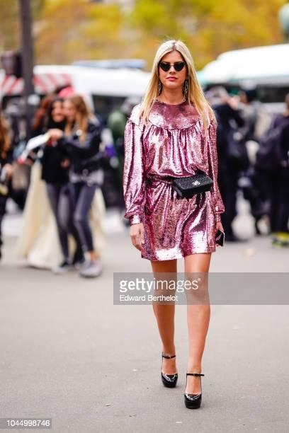 Lala Rudge wears a pink glitter shiny dress a black belt bag outside Miu Miu during Paris Fashion Week Womenswear Spring/Summer 2019 on October 2...