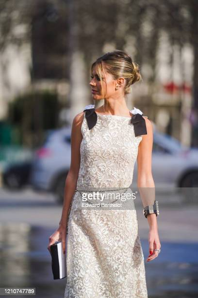 Lala Rudge wears earrings, a bracelet with pearls, a white dress with floral embroidery, a clutch, outside Chanel, during Paris Fashion Week -...