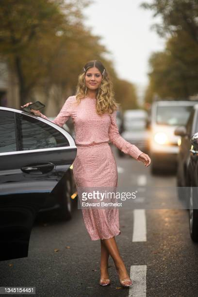 Lala Rudge wears silver and rhinestones hair clips, a pale pink gold nailed / studded long sleeves t-shirt, a matching pale pink gold nailed /...