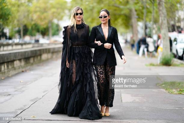 Lala Rudge wears sunglasses earrings a long transparent long sleeves ruffled black dress A guest wears earrings sunglasses a black lace jacket with...